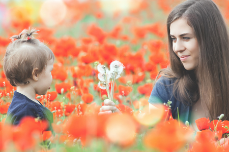 funy: Children - flowers of life. Mother givs funny child a flower of dandelion. Outdoor, poppy field. Baby girl. Spring. ?hildrens Day celebrating on first June, 1 or 14 November