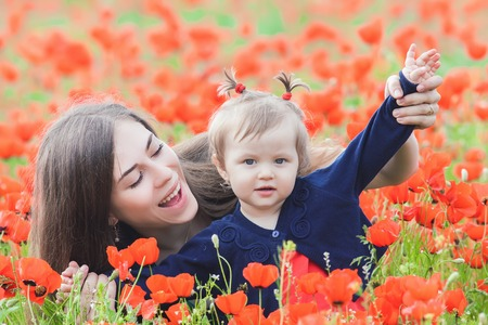 funy: Image of mother holding a funny child outdoor, flying above the poppy flowers field. Happy Family Values. Baby girl and mom. Mothers care is most important in baby lfve. Stock Photo