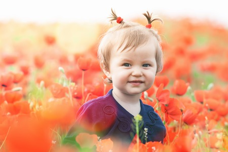 funy: Children - flowers of life. Funny child holding a flower at outdoor at poppy field. Baby girl. Spring. ?hildrens Day celebrating on first June, 1 or 14 November