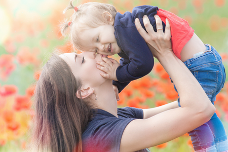mothercare: Mother holding a funny child outdoor at poppy flowers field. Happy Family Values. Baby girl and mom. Mothers care is most important in baby lfve. Mom kissing kid. Spring. ?hildrens Day, Mothers Day Stock Photo