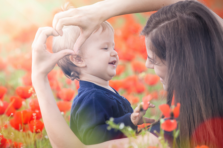 mothercare: Mother with funny child outdoor at poppy flowers field. Happy Family Values. Baby girl and mom. Mothers care is most important in baby lfve. Kid. Spring. ?hildrens Day, Mothers Day. Heart symbol