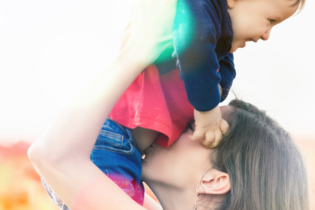 funy: Mother with funny child outdoor at poppy flowers field. Children - flowers of life. Baby girl and mom. Mothers care is most important in baby lfve. Mom kissing kid. ?hildrens Day, Mothers Day