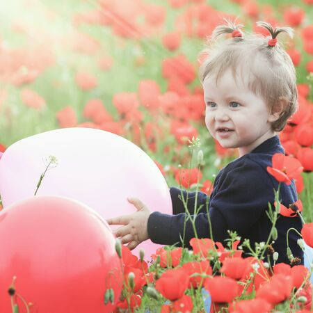 funy: Children - flowers of life. Funny child holding a balloon outdoor at poppy field. Baby girl. Spring. ?hildrens Day celebrating on first June, 1 or 14 November