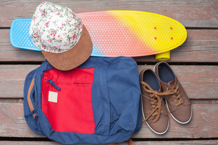 skateboard shoes: Things for skateboarding on a wooden background. Skateboard, shoes, sneakers, cap, bag or backpack. Accessories for outdoor activities. Summer Adventure Stock Photo