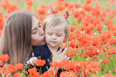 funy: Mother holding a funny child outdoor at poppy flowers field. Happy Family Values. Baby girl and mom. Mothers care is most important in baby life. Mom kissing kid. Spring. Childrens Day, Mothers Day