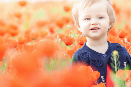 funy: Children - flowers of life. Funny child holding a flower at outdoor at poppy field. Blurred foreground. Baby girl. Spring. Childrens Day celebrating on first June, 1 or 14 November