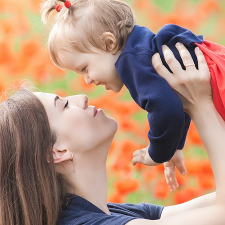 mothercare: Closeup Mother holding a funny child outdoor at poppy flowers field. Happy Family Values. Baby girl and mom. Mothers care is most important in baby life. Mom kissing kid. Spring. Childrens Day, Mothers Day