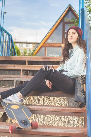 tenager: Hipster skateboarder girl with skateboard outdoor sitting on the stairs. Skatebord at city, street. Cool, Funny Tenager. Austria. Skateboarding at Summer