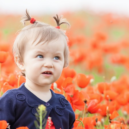 funy: Children - flowers of life. Funny child holding a flower at outdoor at poppy field. Baby girl. Spring. Childrens Day celebrating on first June, 1 or 14 November Stock Photo