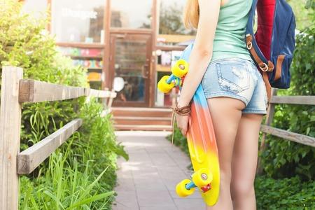 tenager: Close-up fashion skateboarder girl with skateboard outdoor near shop. Skatebord at city, street. Cool, Fun Tenager. Skateboarding at Summer