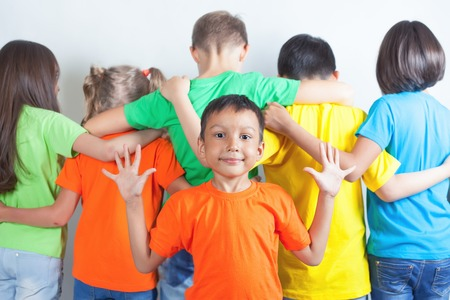 litle: Group of friendly childrens like a team together. With funny litle indian boy shows five gesture. Playgrounds. Friendship. Kids. Conceptual image