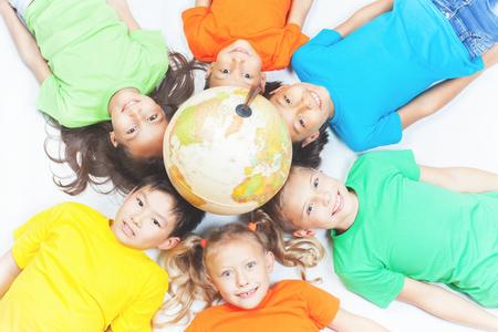 Gruppe internationaler glückliche Kinder. Liegen mit Globus Erde und Blick in die Kamera. Lächelnd. Schulkinder lernen Geographie. Multi ethnische Menschen. Welt. Ökologie. Reine Erde. Internationalen Tag des Kindes Standard-Bild - 56824865