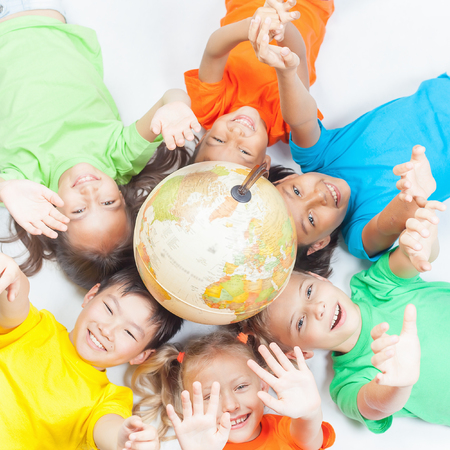 Group of international funny kids. Lying with globe earth, looking up at camera. Smiling. School children learn geography. Multi Ethnic people. World. Ecology. Pure earth. International Children's Day Stockfoto
