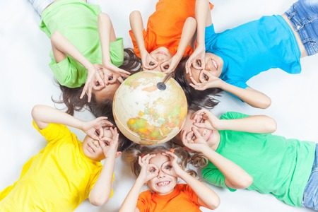 Group of international funny kids with globe earth. Fly gesture. Smiling. School children learn geography. Travel and adventure, world. Ecology. Pure earth. International Childrens Day