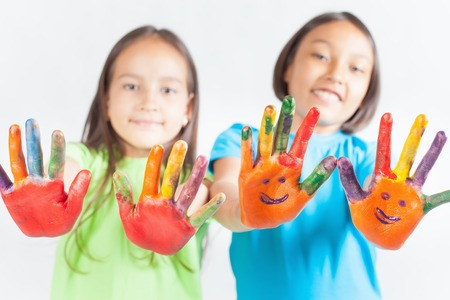 painted hands: Happy kids with painted hands on a white background. International Childrens Day. Painting, occupation