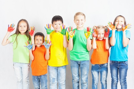 Happy kids with painted hands smiling and posing at white background. Funny children. International Childrens Day. Indian, asian, caucasian - multiracial ethnicity Stock Photo