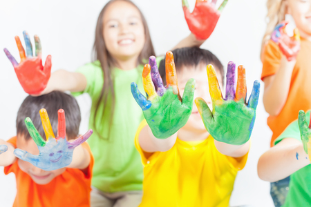 Happy kids with painted hands on a white background. International Children's Day. Painting, occupation Zdjęcie Seryjne - 56824872