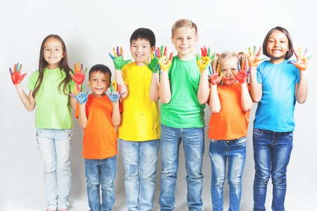 kids painted hands: Happy kids with painted hands smiling and posing at white background. Funny children. International Childrens Day. Indian, asian, caucasian - multiracial ethnicity Stock Photo