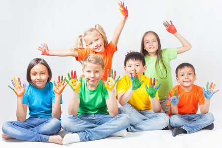 Happy kids with painted hands smiling and posing at white background. Funny children. International Children's Day. Indian, asian, caucasian - multiracial ethnicity 写真素材