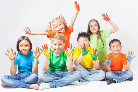 Enfants heureux avec les mains peintes en souriant et posant au fond blanc. enfants drôles. Journée internationale des enfants. Indienne, asiatique, caucasien - ethnique Banque d'images - 58818978