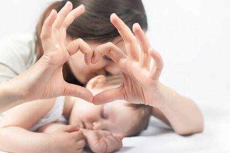 corazon en la mano: Feliz madre y el bebé. Símbolo del corazón por las manos. concepto de cuidado de la familia. AMOR. sueño saludable. Cuidado de la salud. Médico. el cuidado de la madre es lo más importante en el bebé vivo. Fondo blanco