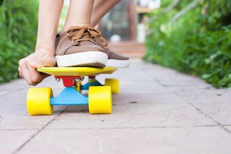 teen legs: Close-up skateboarder boy riding outdoor.