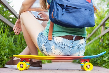 tenager: Close-up of skateboarder girl sitting on skateboard outdoor.