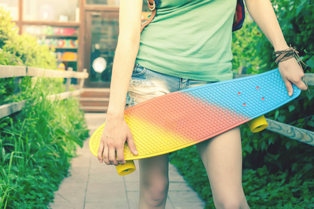 tenager: Close-up fashion skateboarder girl with skateboard outdoor near sport shop. Skatebord at city, street. Cool, Fun Tenager. Skateboarding at Summer