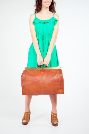 allowance: Woman holding hand luggage at the airport terminal. Suitcase sale. Tourism. Vintage tourist bag. Passenger. Airlines. Weight and baggage dimensions. Baggage allowance