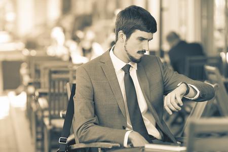 punctuality: Imagen renacimiento retro del tiempo el hombre hermoso que mira el reloj. Y espera sentado en el caf� de la acera al aire libre. Ejecutivo de negocios vestidos con trajes de moda. Hombre con estilo. Puntualidad