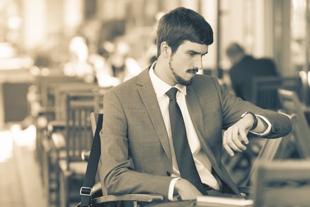 punctuality: Retro revival image of handsome man looking time at watch. Waiting and sitting at sidewalk cafe outdoors. Executive businessman dressed in fashion costume. Stylish man. Punctuality