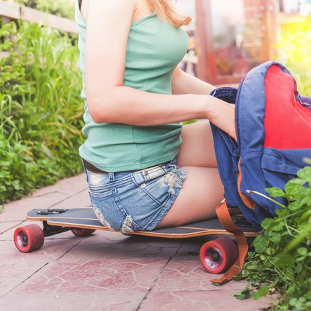tenager: Close-up of skateboarder girl sitting on skateboard outdoor and using her backpack. Dressed in shorts, wearing a sport backpack. Skatebord at city street. Tenager. Skateboarding at Summer. Schoolgirl Stock Photo