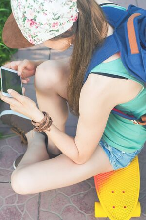 tenager: Close-up of skateboarder girl sitting on skateboard outdoor and using mobile phone. Dressed in shorts, wearing a sport backpack. Skatebord at city street. Tenager. Skateboarding at Summer. Schoolgirl Stock Photo