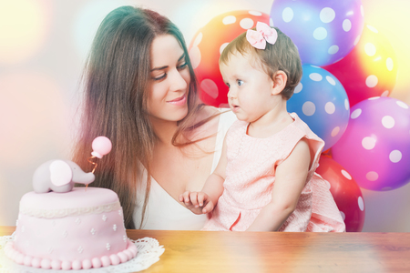 wish desire: Mother with cute baby girl celebrating first bithday. Cake is surprise for child. Make a first wish. Desire. Funny