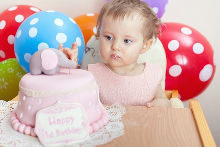 wish desire: Cute baby celebrating first birthday - one year and eating cake. Child with many balloons! Make a first wish. Desire