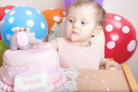 overeat: Cute baby celebrating first birthday - one year and eating cake. Child with many balloons! Make a first wish. Desire