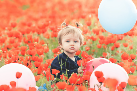 funy: Children - flowers of life. Funny child holding a balloon outdoor at poppy field. Baby girl. Spring. Childrens Day celebrating on first June, 1 or 14 November