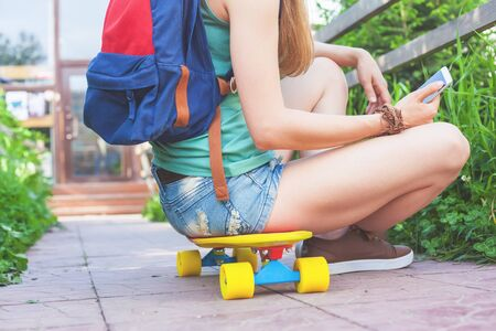 tenager: Close-up of skateboarder girl sitting on skateboard outdoor. Using mobile phone. Dressed in shorts and wearing a sport backpack. Tenager. Skateboarding at Summer. Schoolgirl