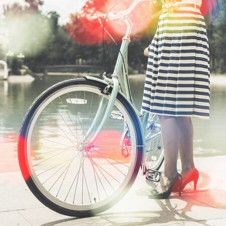 Vintage image of young girl standing near fence near vintage city bike at the park. Happy vacation travel at European city, Paris photo