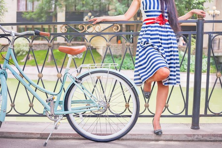 Vintage image of young hipster girl standing near fence near vintage city bike at the park. Freedom teenager with her happy vacation travel at European city, Paris photo