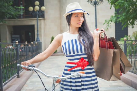 Fashion woman dressed in striped dress with bags and vintage bike has shopping travel to Italy, Milan. Shoping. Wuman has happy vacation travel to Europe photo