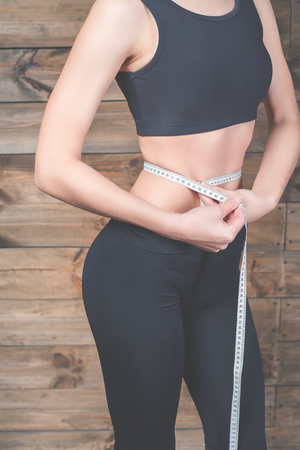 centimeters: Attractive girl measure the waist, centimeters tape. Slim stomach do abdominal exercises. Workout exercise at home to lose weight Stock Photo