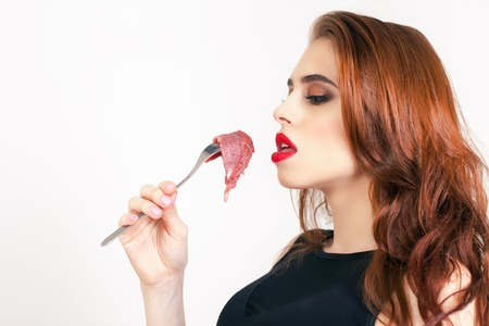 expiration date: Image of woman eating raw meat at the white background. Cooking. Healthy eating. Meat recipes, expiration date, shelf life Stock Photo