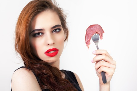 expiration date: Image of woman holding fork with piece of meat at the restaurant. Cooking. Healthy eating. Meat recipes, expiration date, shelf life
