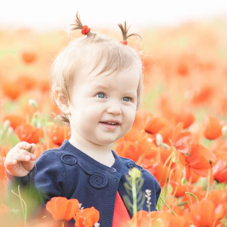 Children - flowers of life. Funny child holding a flower at outdoor at poppy field. Blurred foreground. Baby girl. Spring. Childrens Day celebrating on first June, 1 or 14 November