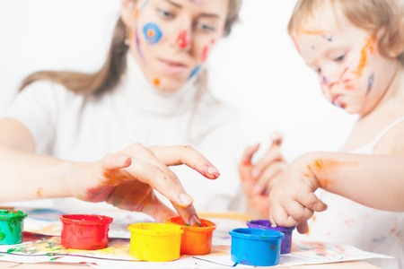 Mom and baby draws with colored inks. Games with child affect early development. Important to spend enough time with your kids.