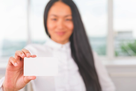 race relations: Asian businesswoman holding a business card for your contacts: mobile phone, fax, email, web site. Relation and communication. White blank with copy space Stock Photo