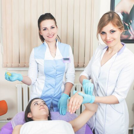sugaring: Facial rejuvenation procedure. Beautiful woman in spa salon receiving epilation using sugar - sugaring. Doctor. Practice for the intern.