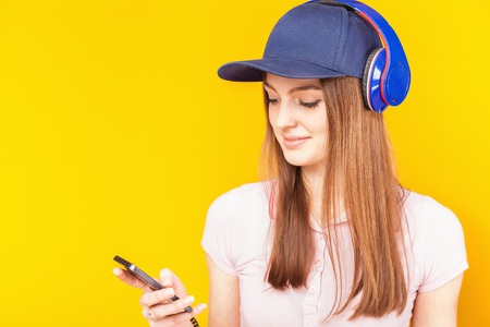 phone cord: Beautiful teenage girl uses a headphones and mobile phone. Fashion student. Shopping. Sms message