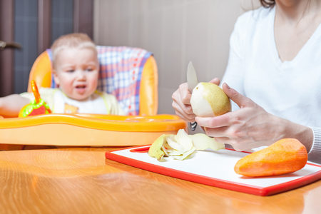 highchair: Mother cuking, preparation of baby food. Food for baby. Recip. Baby care, healthy nutrition, meal. Child sitting on highchair at table. Kitchen, home. Fresh fruit, pear, apple, carrot on the table Stock Photo
